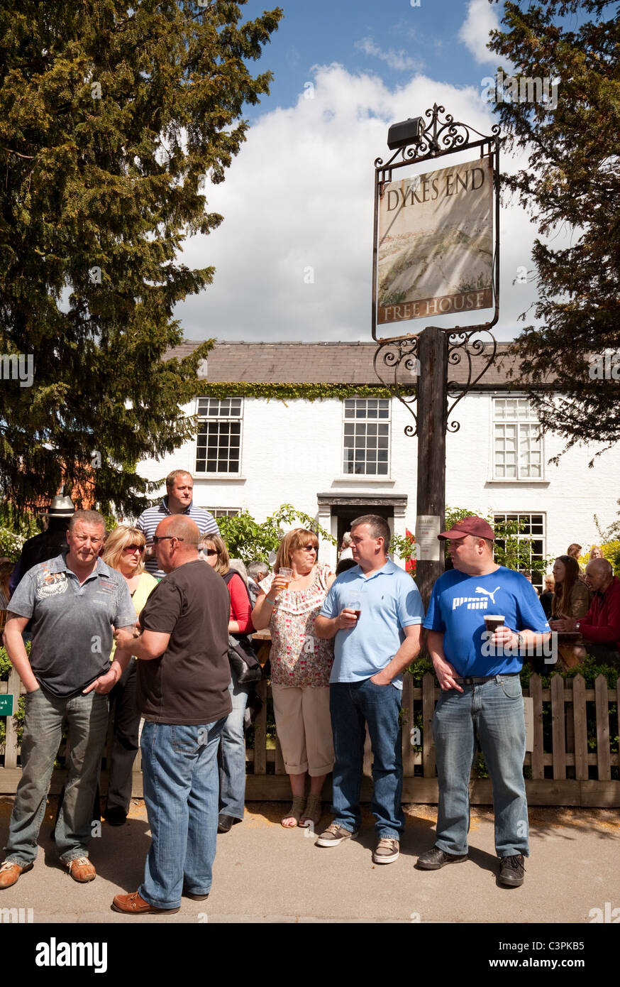 People enjoying a drink at the Dykes End village pub, Reach, Cambridgeshire, UK - Stock Image