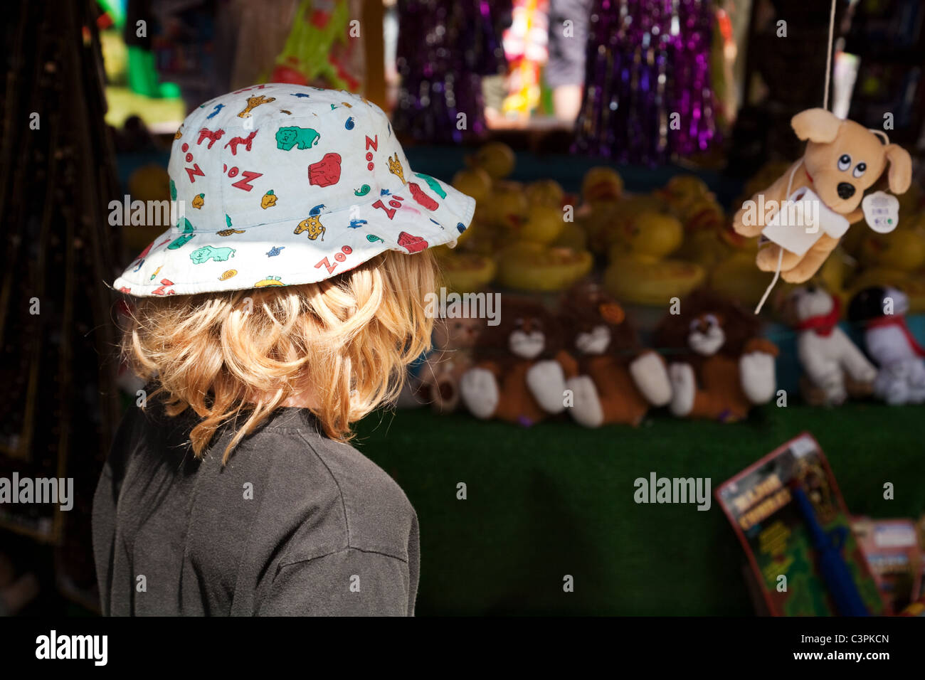 A young child looking longingly at a prize in a stall at the fair, Reach village Cambridgeshire, UK - Stock Image