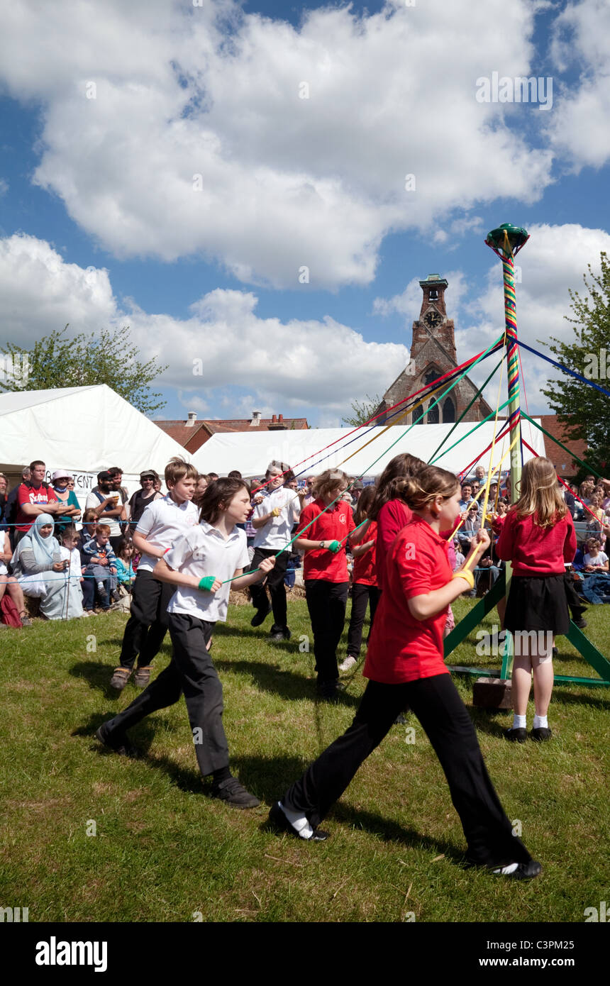 Children from a local primary school dancing round the maypole on May Day at Reach Fair, Reach, Cambridgeshire, - Stock Image