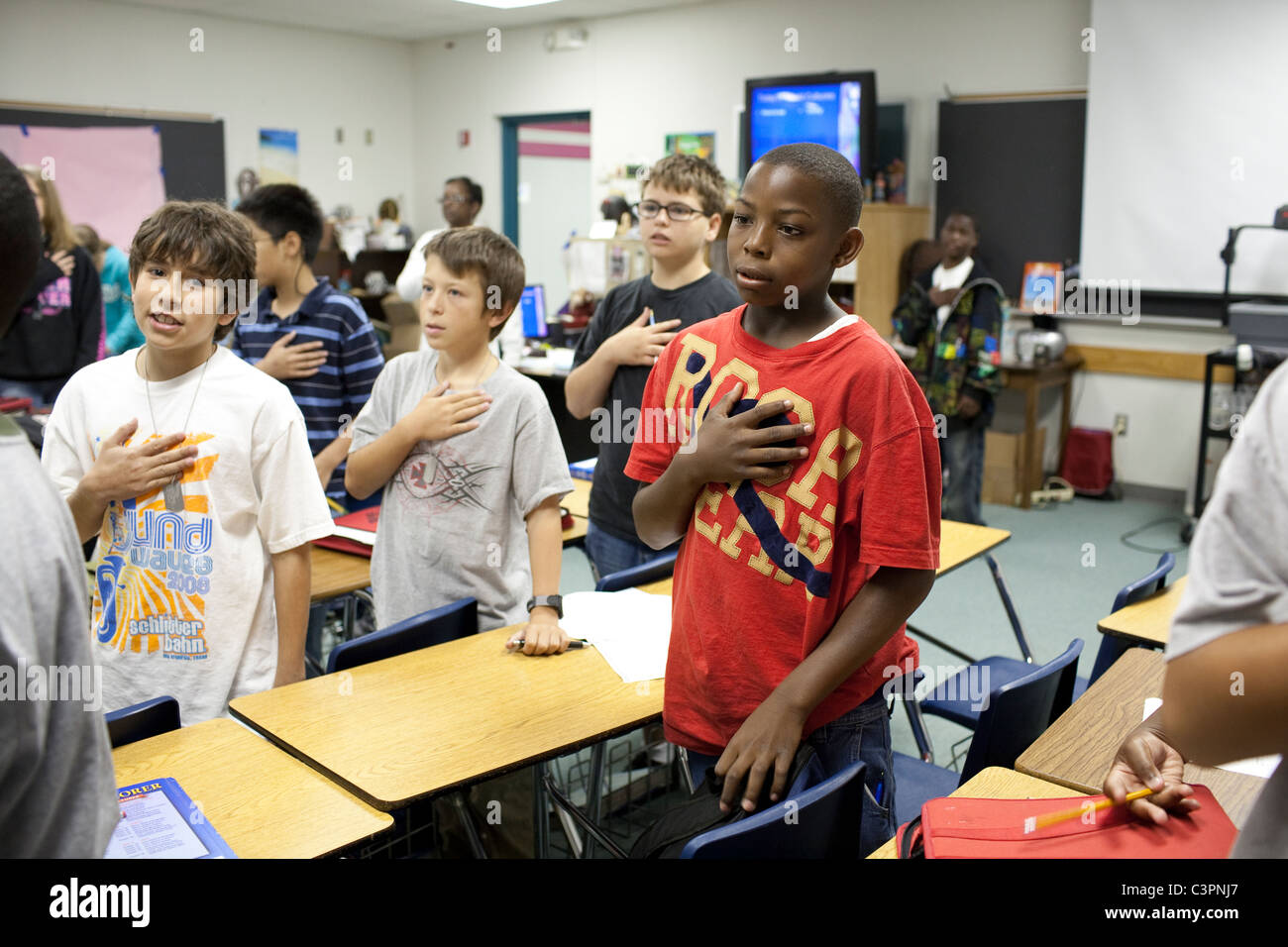 Middle School junior high students stand at beginning of class with hand on heart to recite the pledge of allegiance - Stock Image