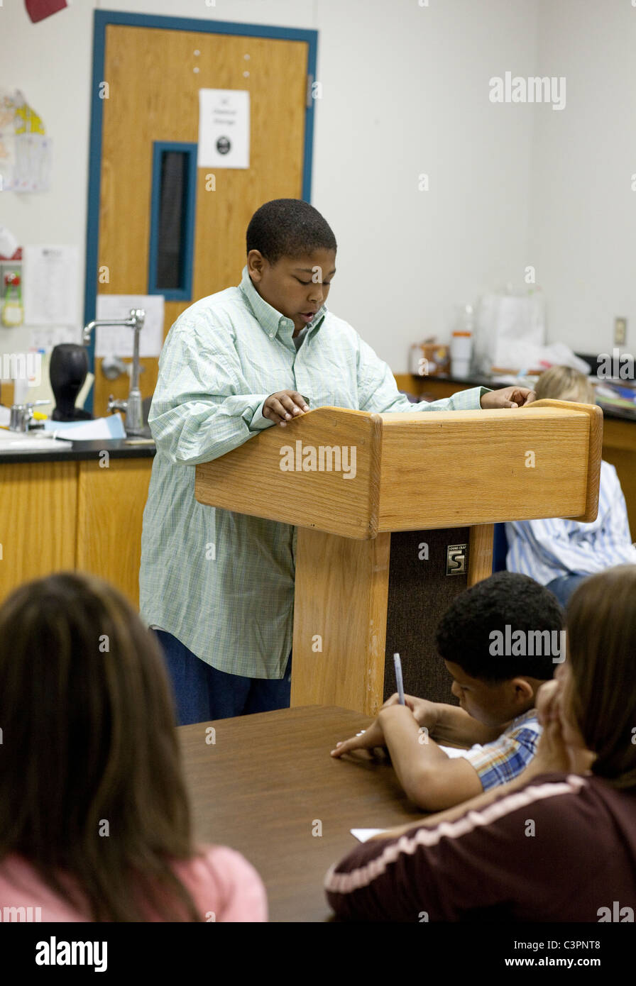 African-American male student reads to classmates from podium in classroom of middle school - Stock Image