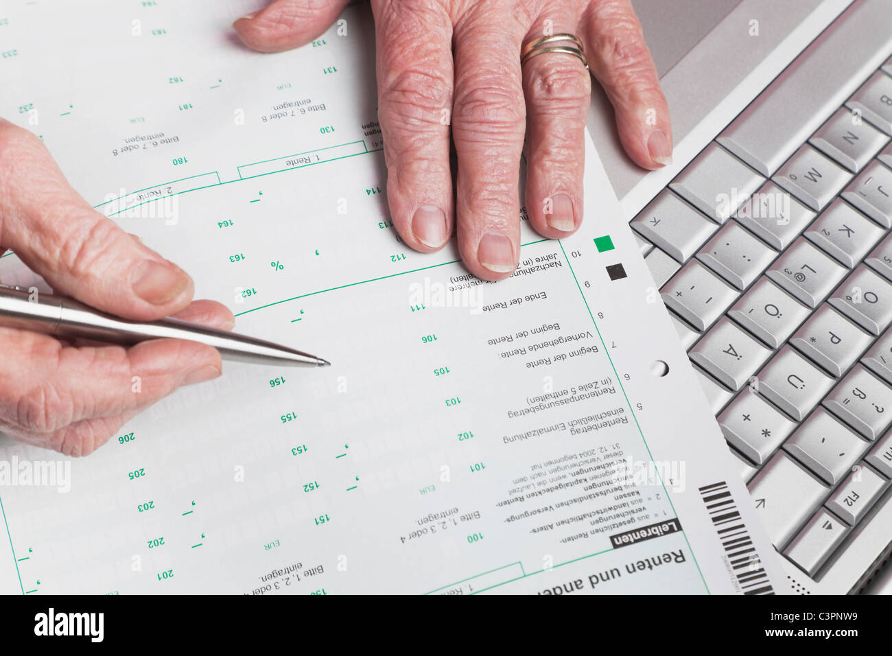 Germany, Senior woman with pension statement and laptop - Stock Image