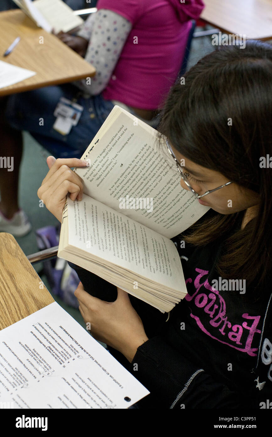Female student wearing glasses reads paperback book up close at her desk in junior high middle school classroom - Stock Image