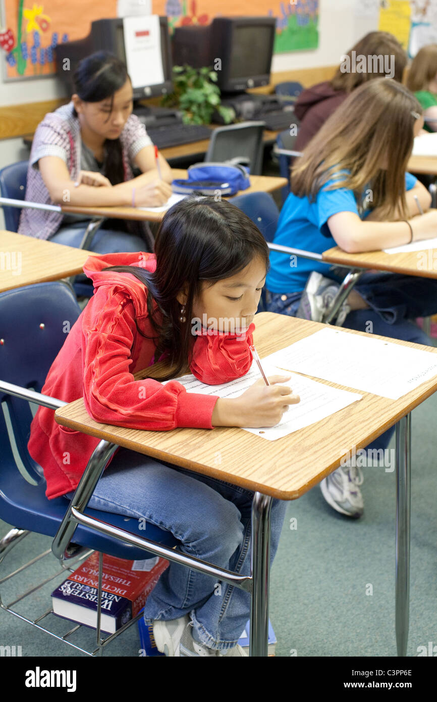 Female Asian-American junior high middle school student writes on paper at her classroom desk - Stock Image