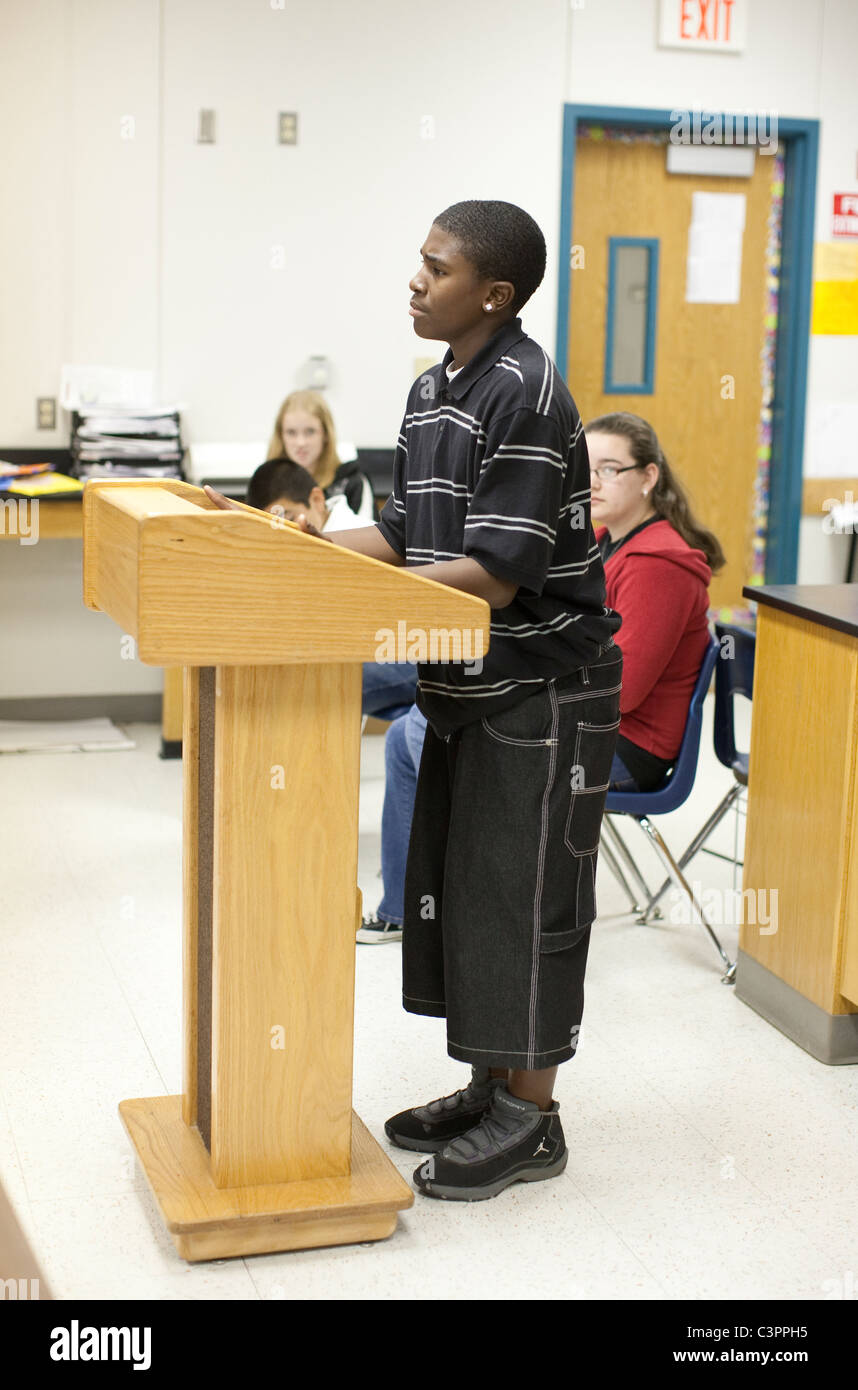 Male African-American junior high school student speaks at podium in classroom in Texas - Stock Image