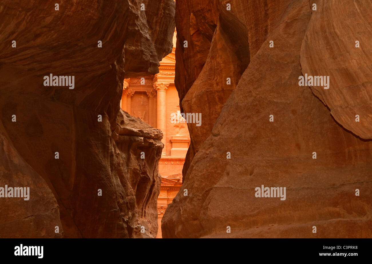 A view of the temple or treasury in Petra, Jordan through the sandstone slot canyon. Stock Photo