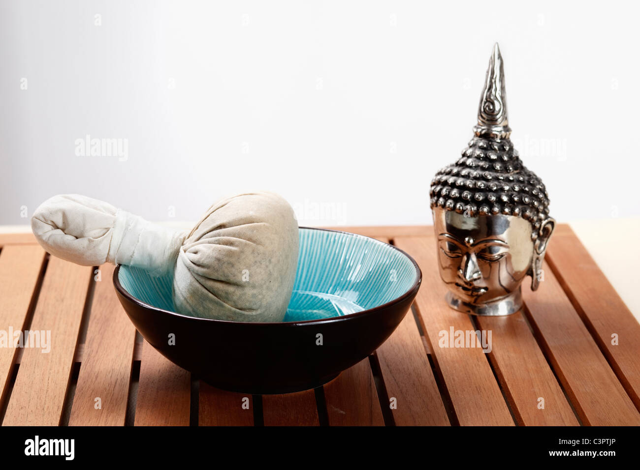 Buddha head with herb pouch in bowl on table - Stock Image