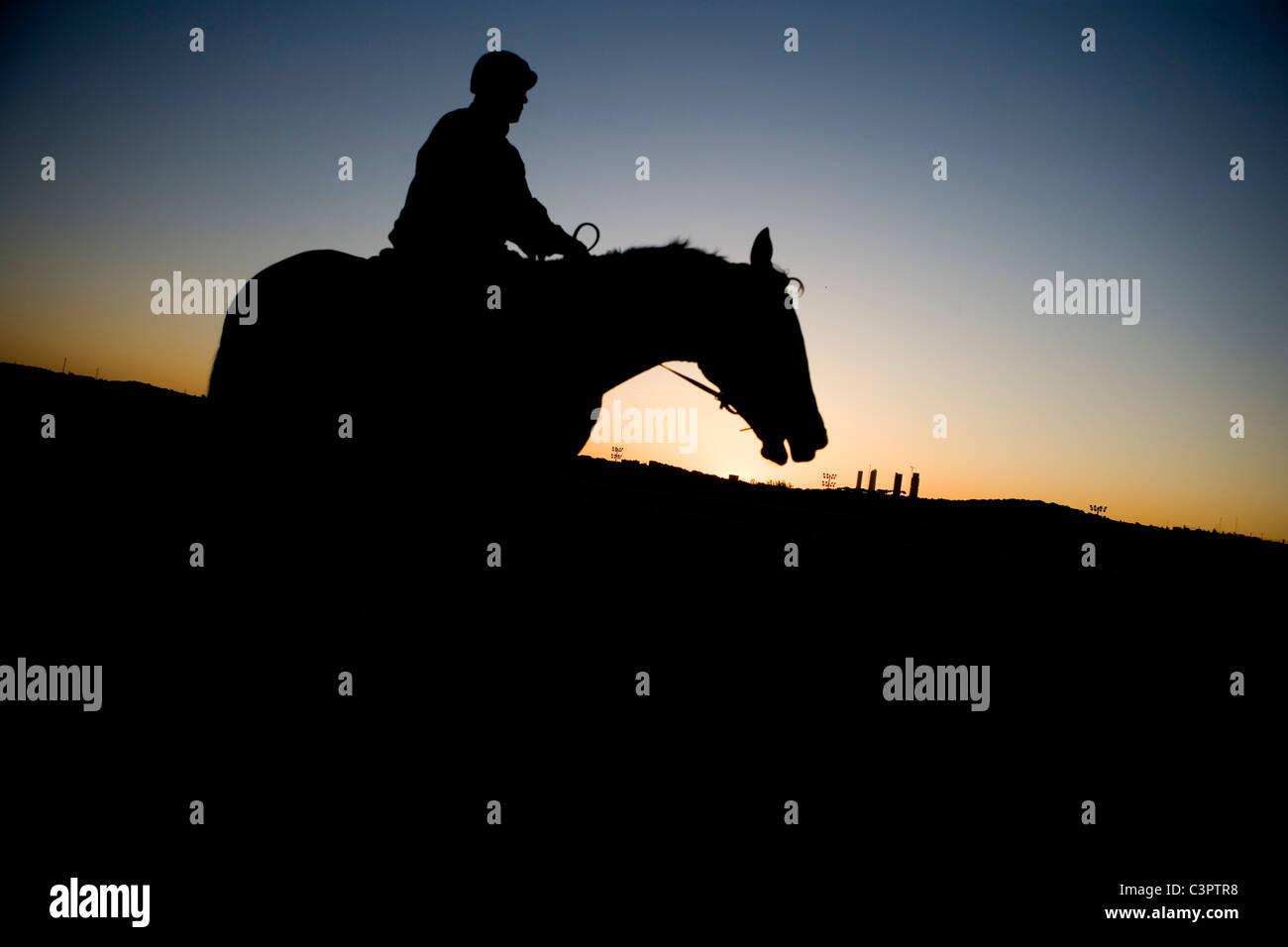 Jockey in silhouette during sunrise at  Hipodromo de la Zarzuela in Madrid (Spain). - Stock Image