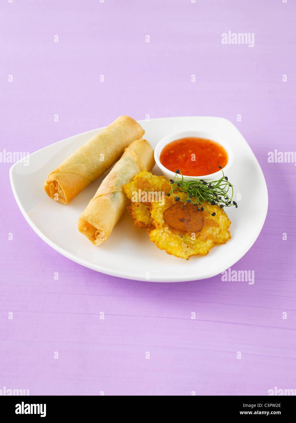 Spring rolls and plantain crisps with chili sauce - Stock Image