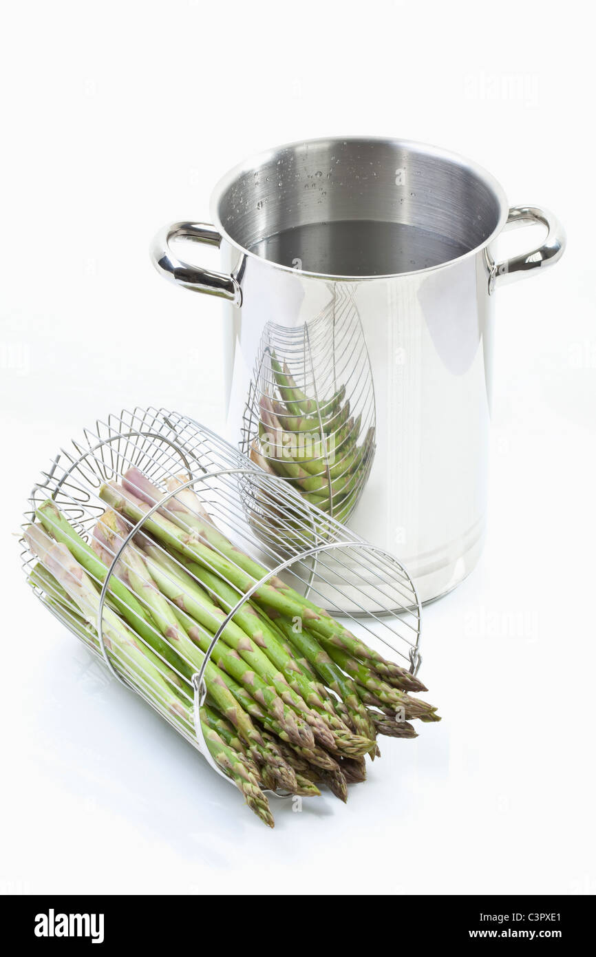 Asparagus in container with cooking pot on white background - Stock Image