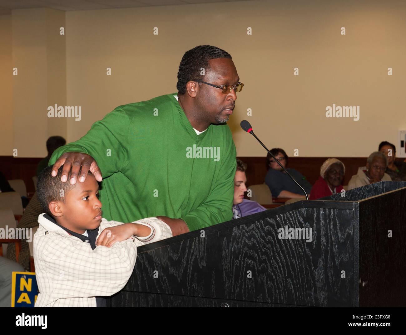 Ramel Smith speaking, hand on son's head, at Nassau County Legislative Redistricting Public Hearing, May 9, - Stock Image