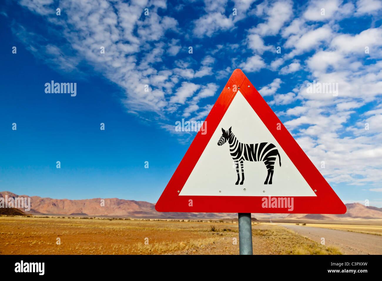 Africa, Namibia, Namib Desert, Close up of animal crossing sign gravelroad through Namib Rand - Stock Image