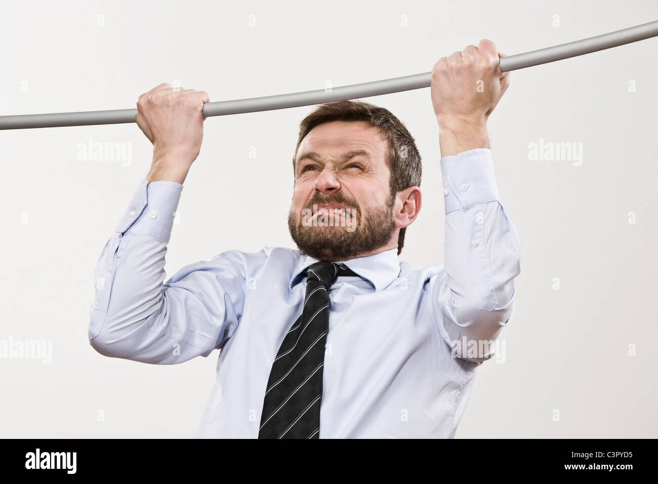 Businessman doing pull-ups, close-up - Stock Image