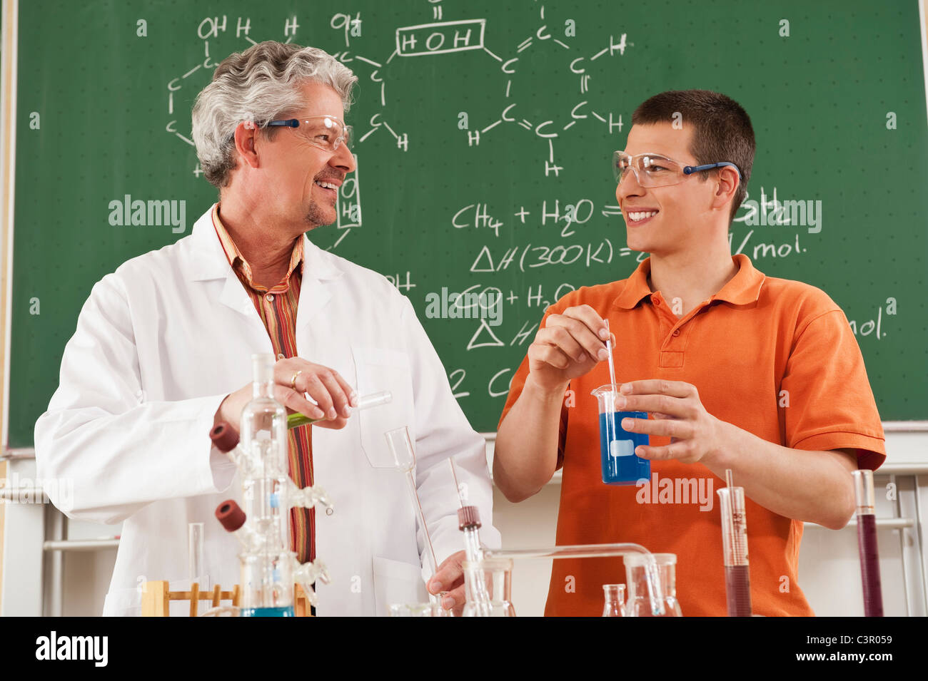 Germany, Emmering, Teacher and student doing experiment in chemistry class, smiling - Stock Image