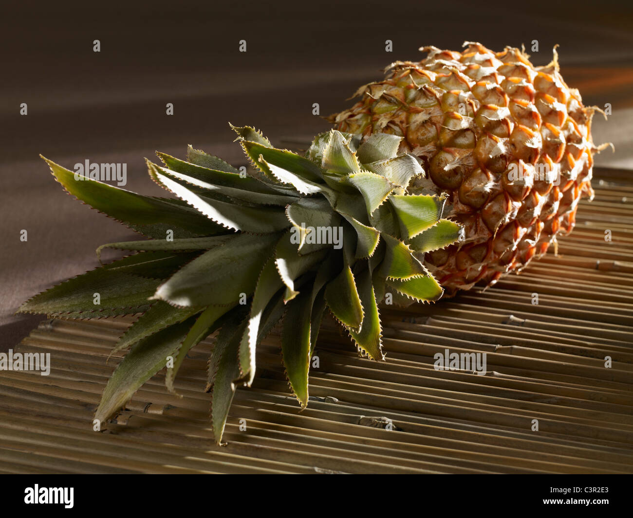 Pineapple on place mat, close-up - Stock Image