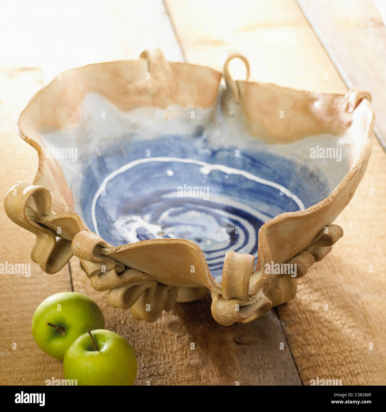 Pottery bowl with granny smith apples - Stock Image