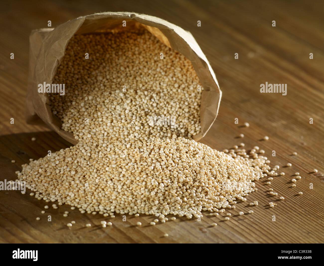 Quinoa grain spilling on wooden surface - Stock Image