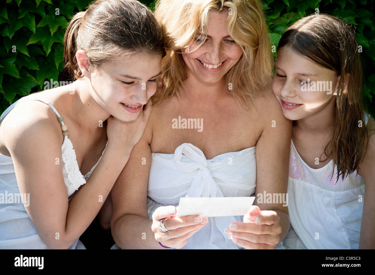 Mum and daughters look at photos - Stock Image