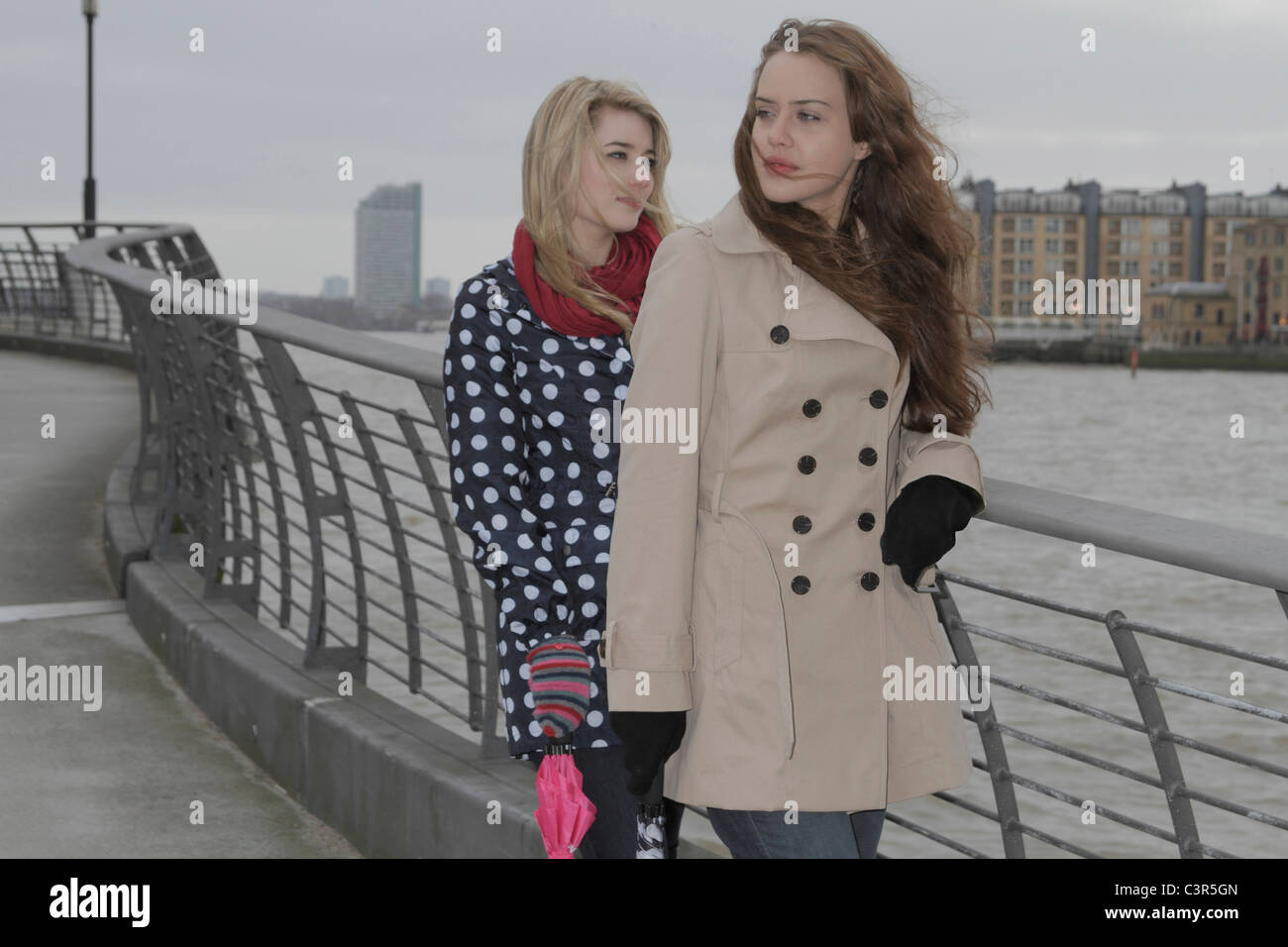 2 young women windswept at river - Stock Image