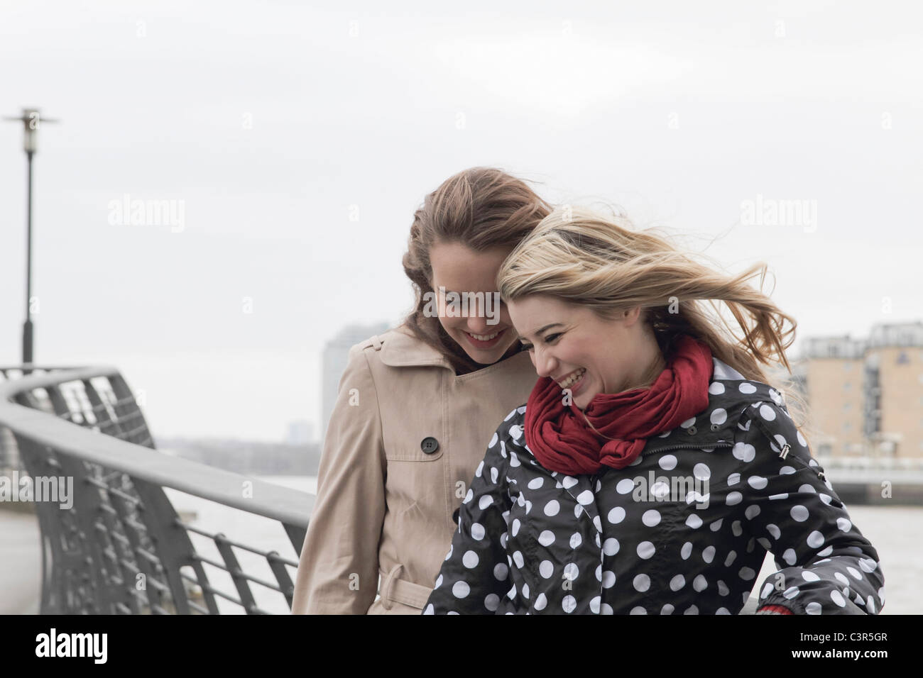 2 young windswept women laughing - Stock Image