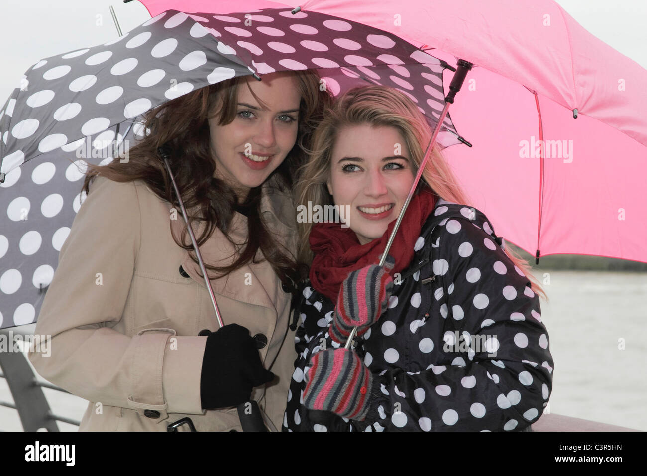 2 young women with umbrellas - Stock Image
