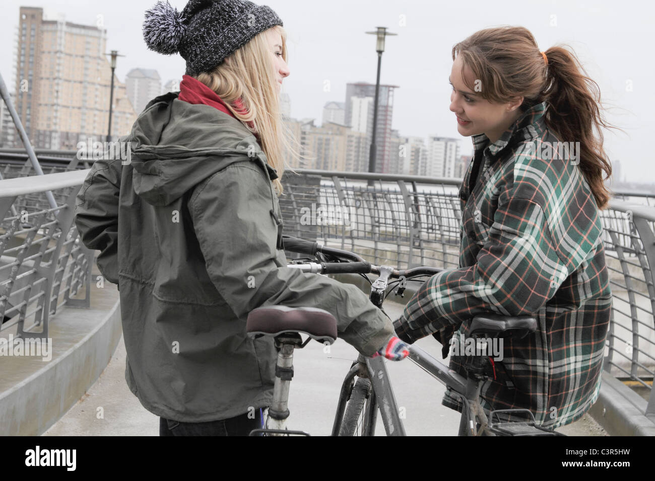 2 young women chatting with push bikes - Stock Image
