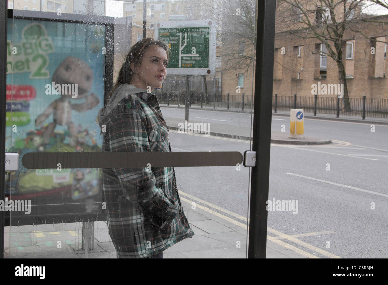 Young woman at bus shelter in rain - Stock Image