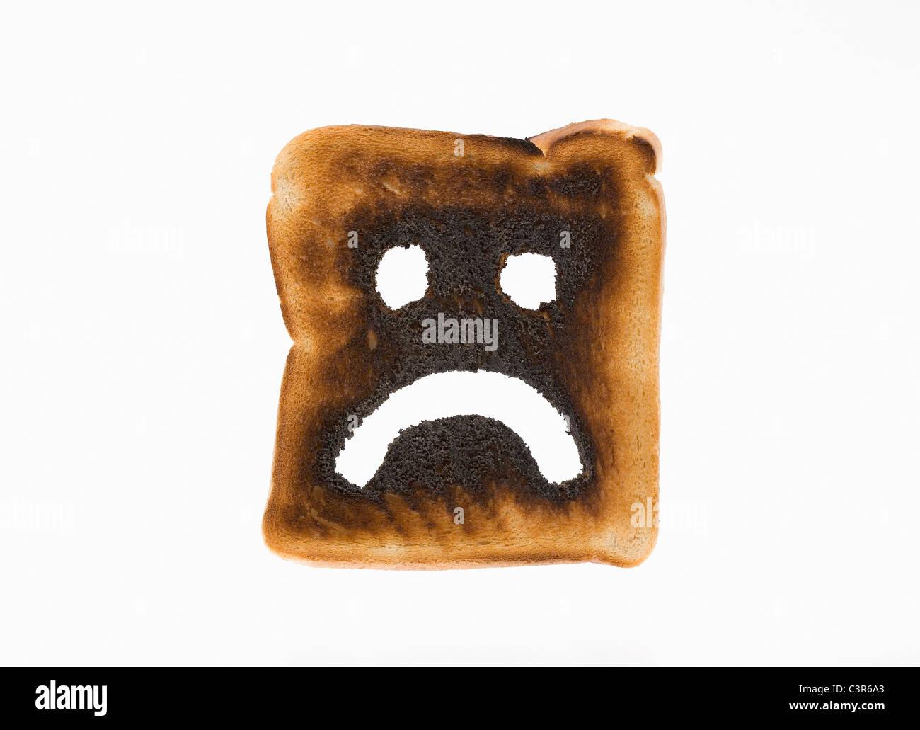 Burnt toast with sad face on it - Stock Image