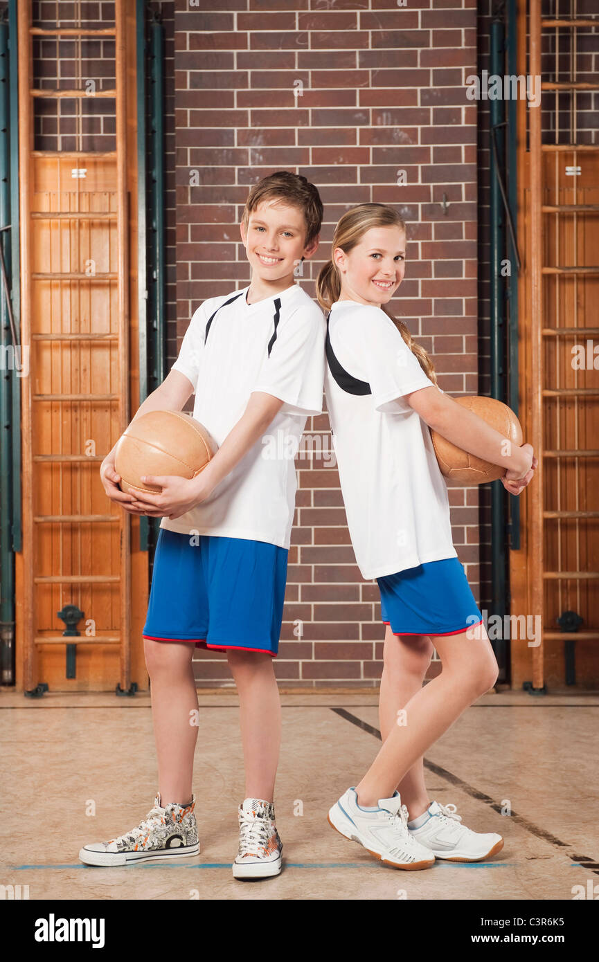 Germany, Emmering, Boy and girl (12-13) holding ball and smiling, portrait Stock Photo