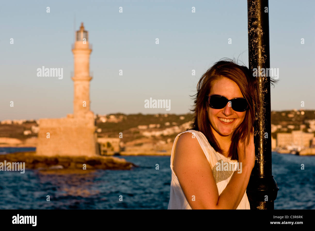 woman smiling at the camera in front of harbour - Stock Image