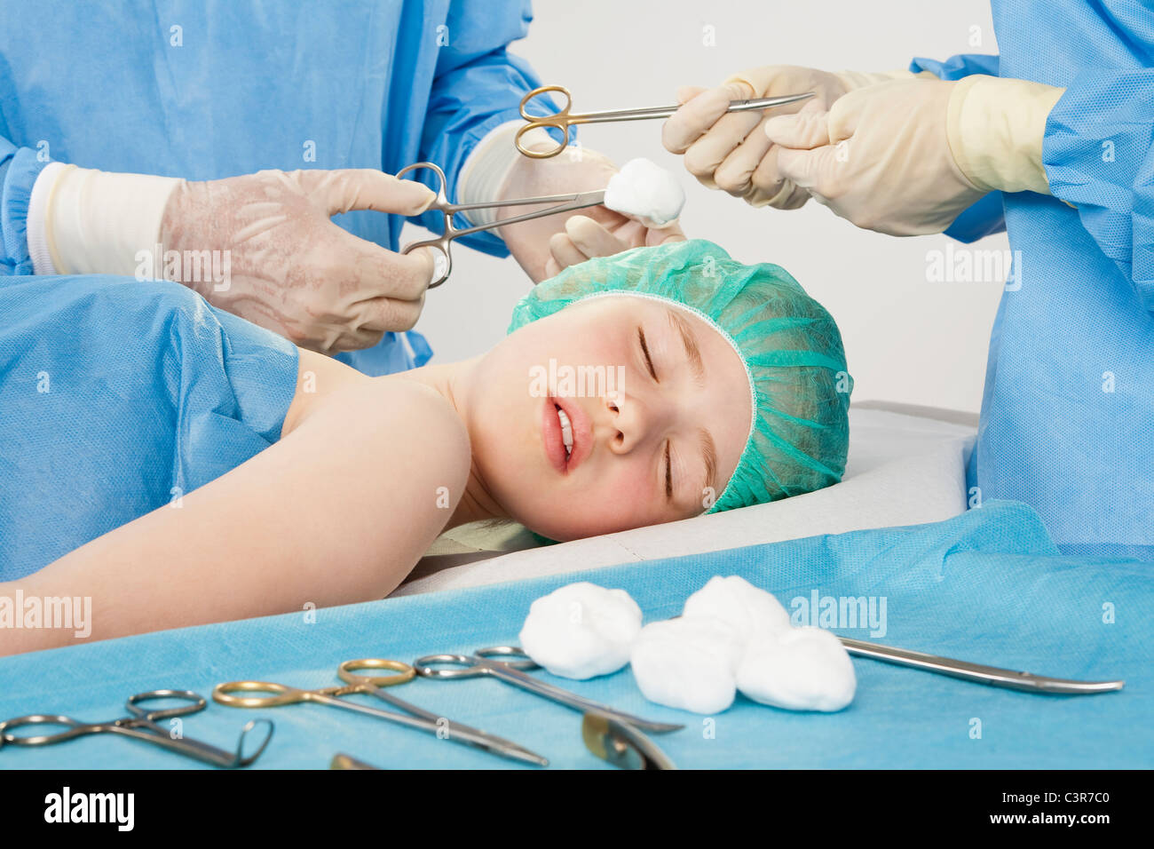 Germany, Munich, Surgeons performing operation - Stock Image