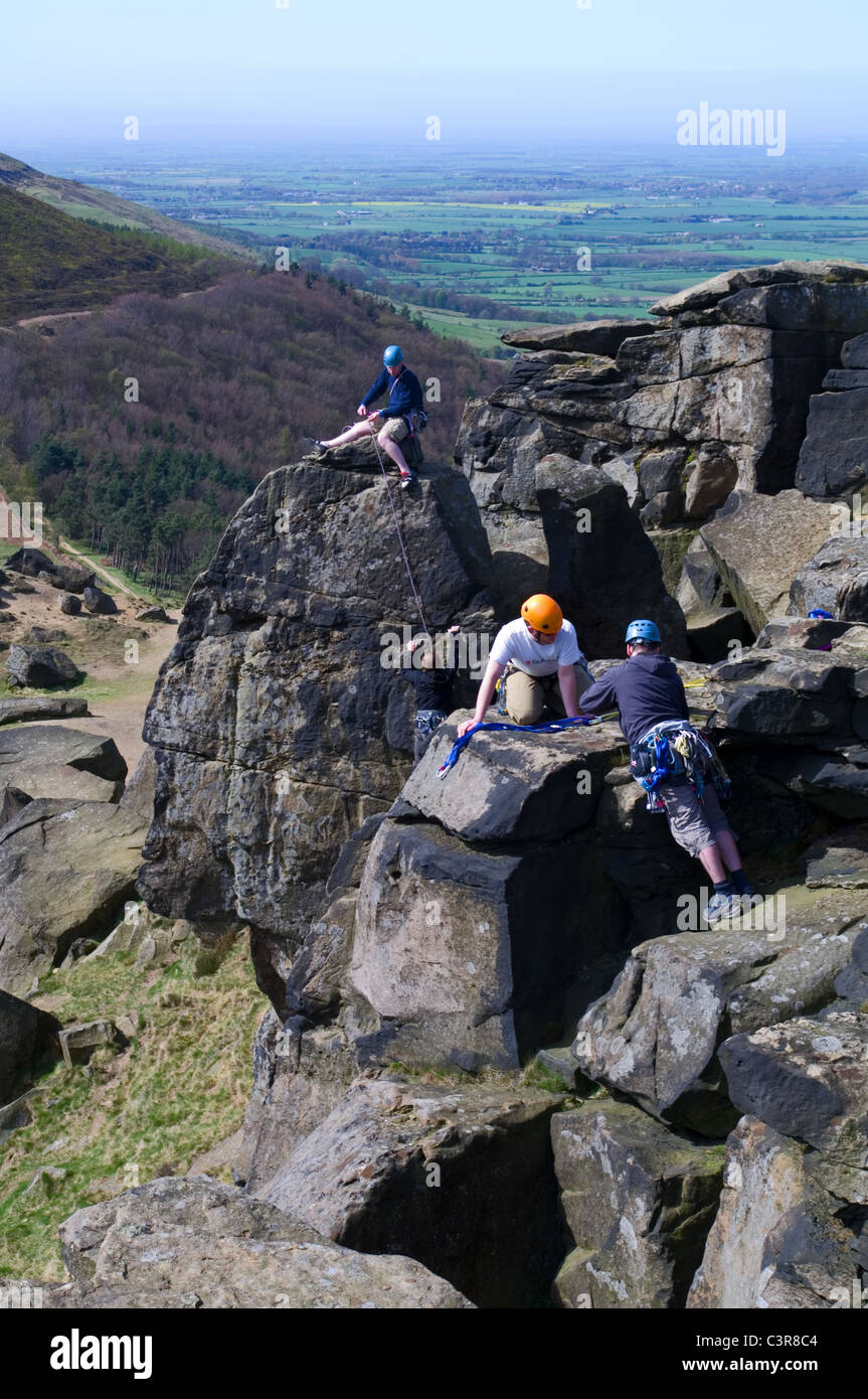 4 rock climbers on the Wainstones, Hasty Bank, the Cleveland Way, overlooking Broughton Plantation and Stokesley - Stock Image