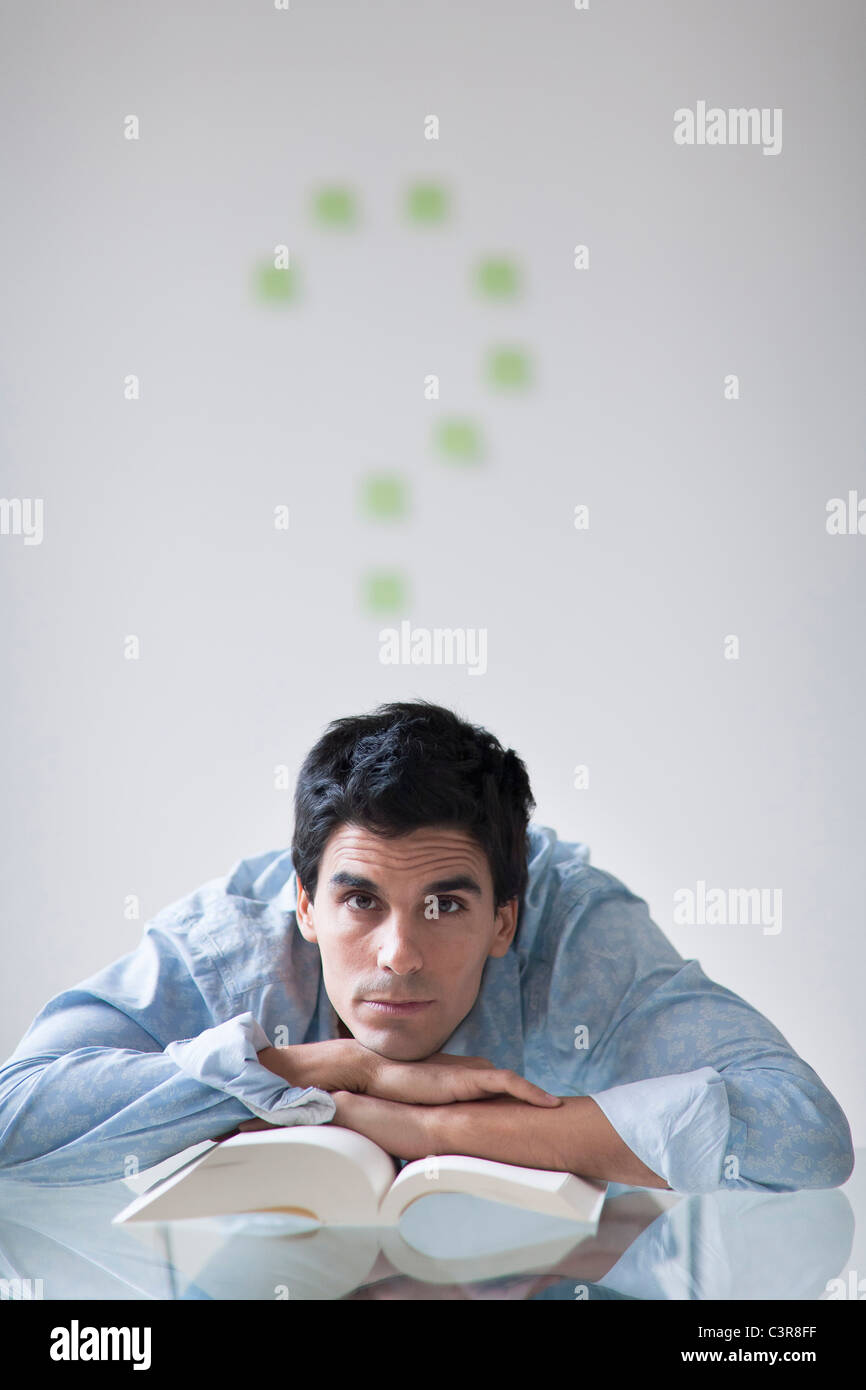 Man with a post-it note question mark above his head - Stock Image
