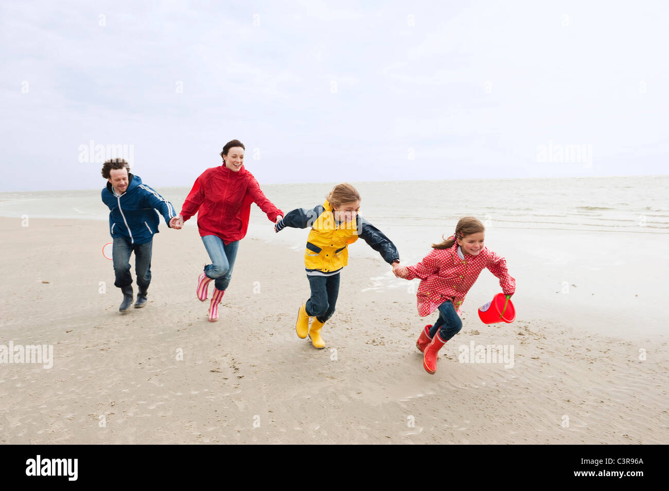 Germany, St. Peter-Ording, North Sea, Family holding hands and running on beach - Stock Image