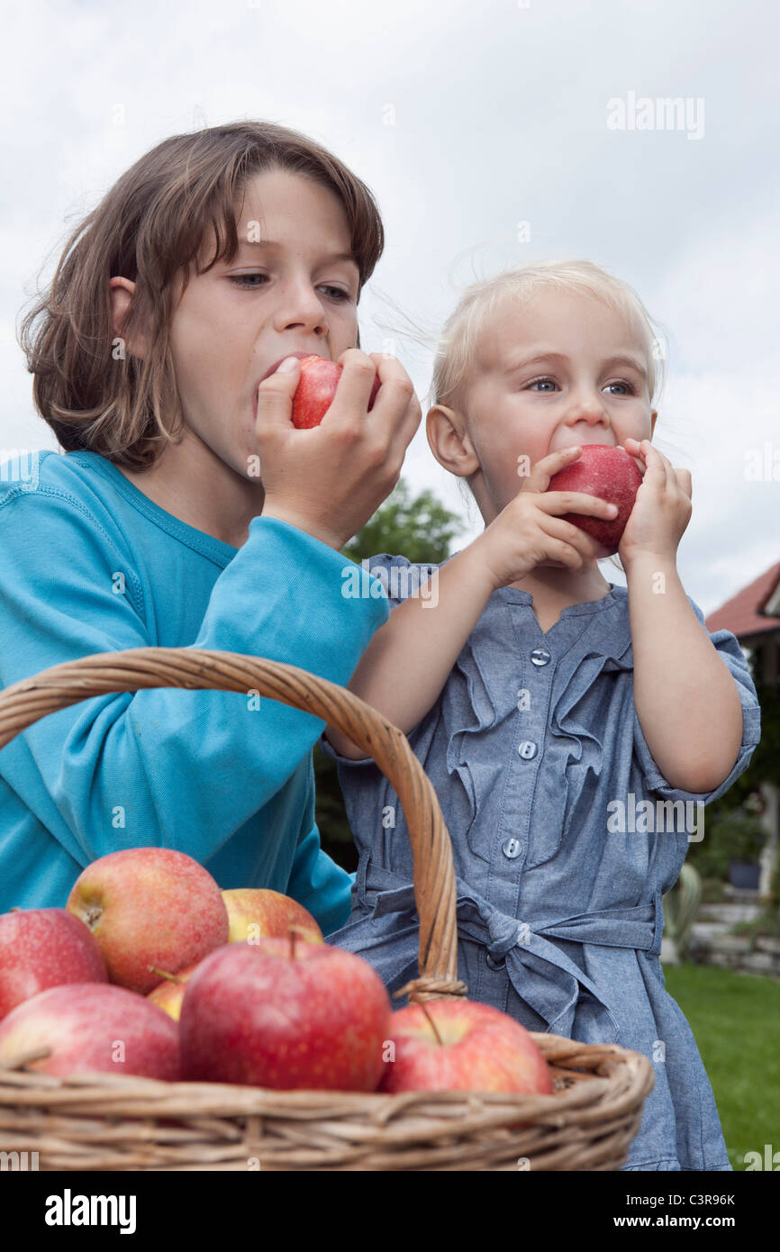 Germany, Munich, Girl (2-3 Years) and boy (10-11 Years ) eating apples - Stock Image