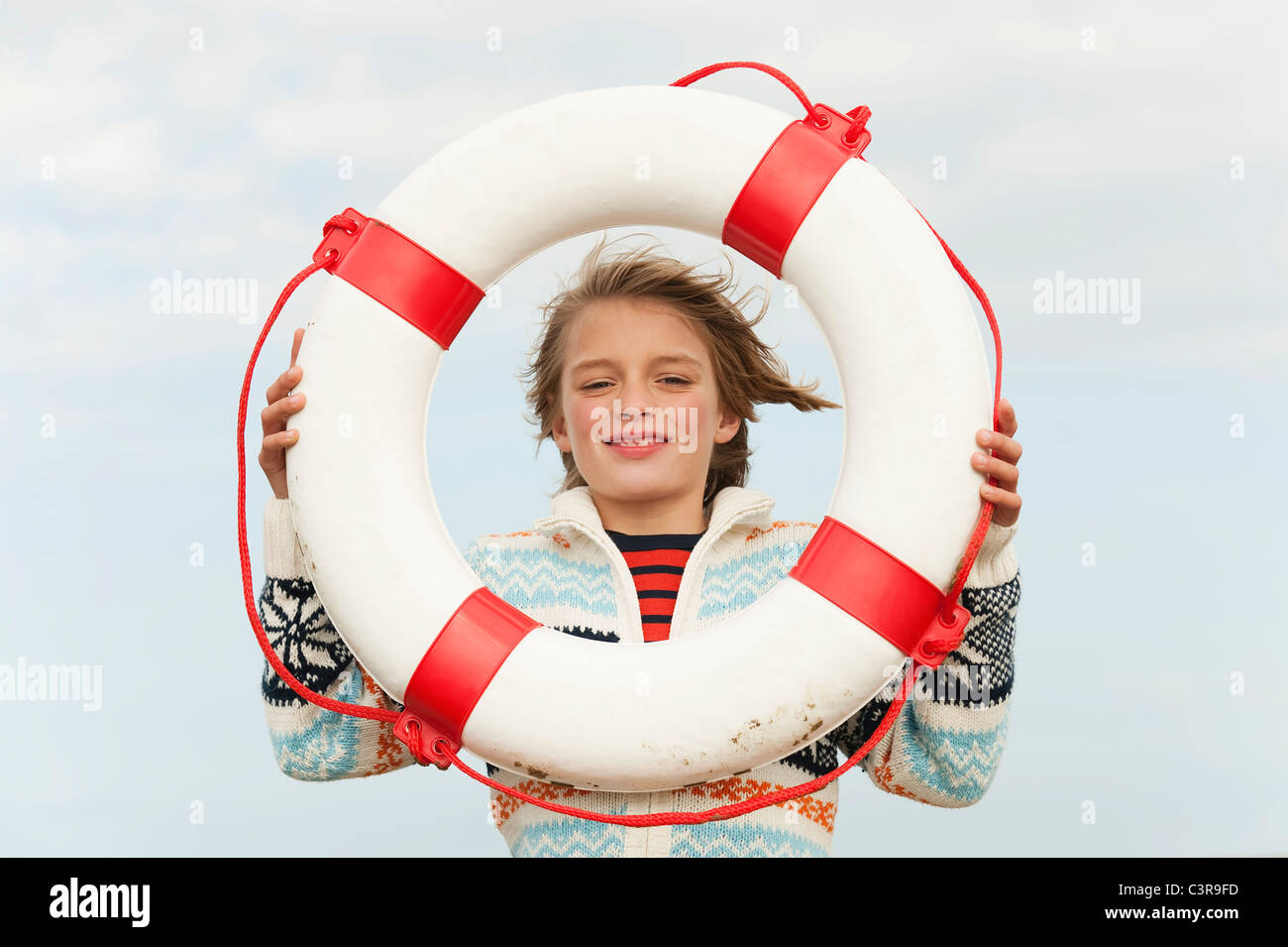 Germany, North Sea, St.Peter-Ording, Boy (8-9) holding life saver at beach, smiling, portrait - Stock Image