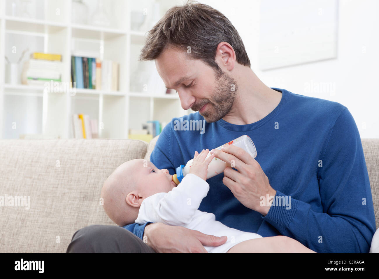 Germany, Bavaria, Munich, Father feeding milk to baby boy (6-11 Months) in living room - Stock Image
