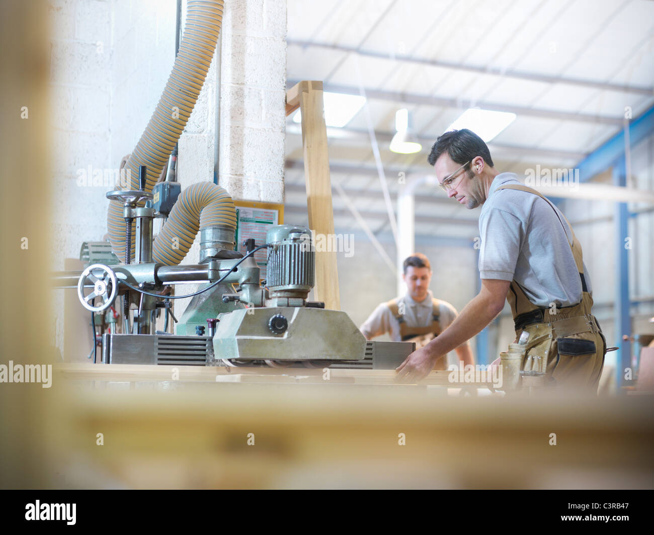 Woodworkers with planing machine - Stock Image