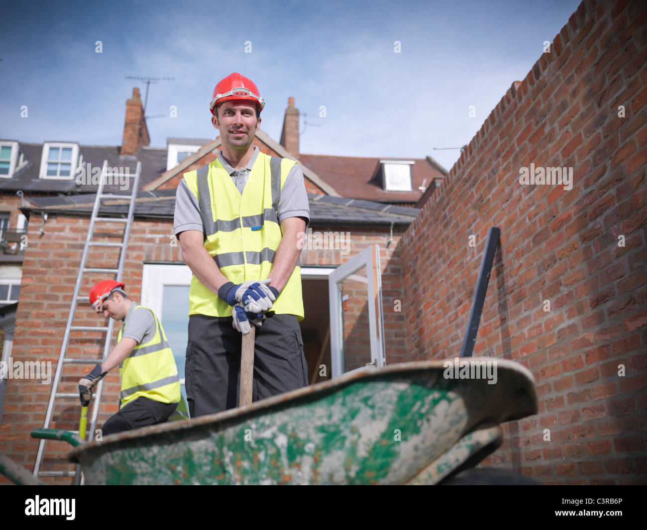 Builders outside house with wheelbarrow Stock Photo