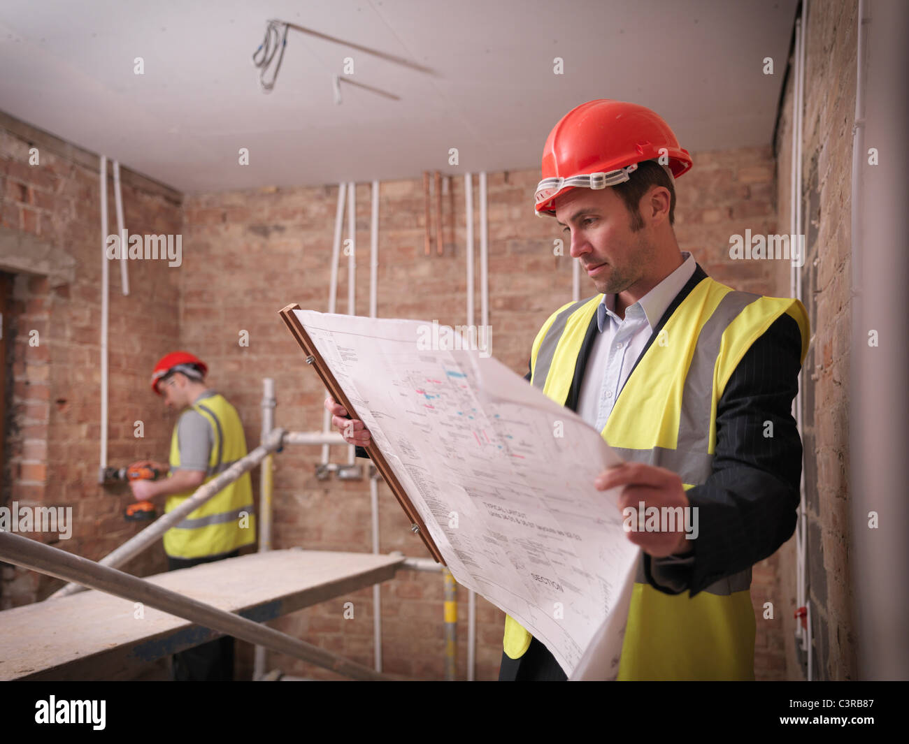 Architect with plans on building site - Stock Image