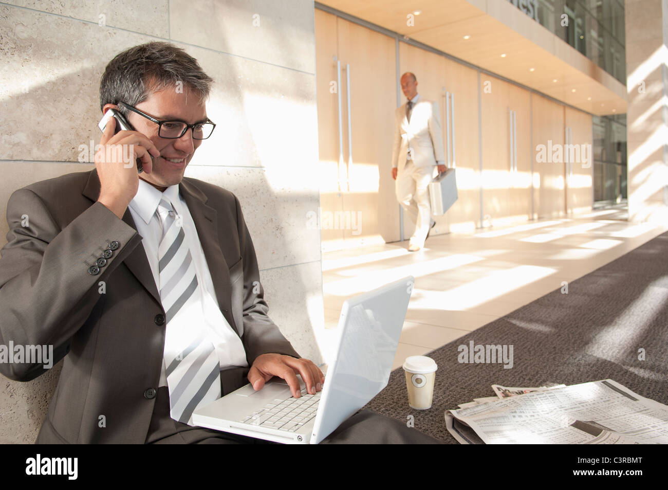 Buisness man on laptop and phone - Stock Image