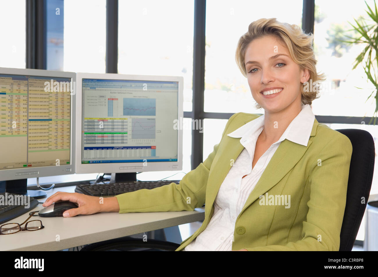 Buisness woman at the computer smiling - Stock Image
