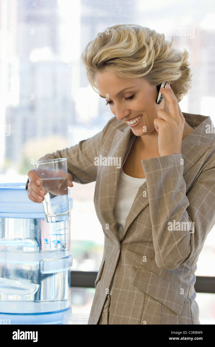 Buisness woman on the phone with water - Stock Image