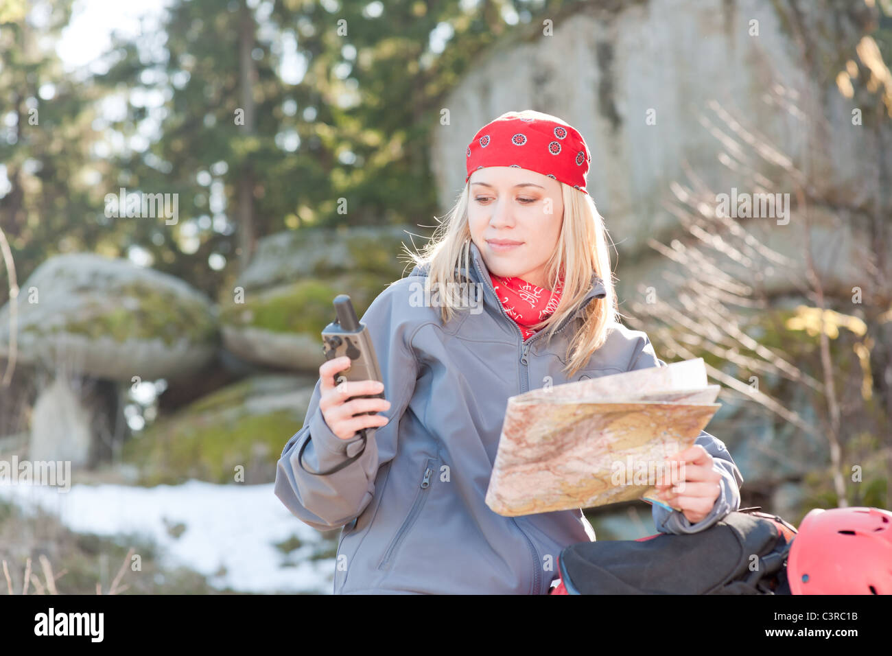 Active young woman backpack search navigation map rock climbing - Stock Image