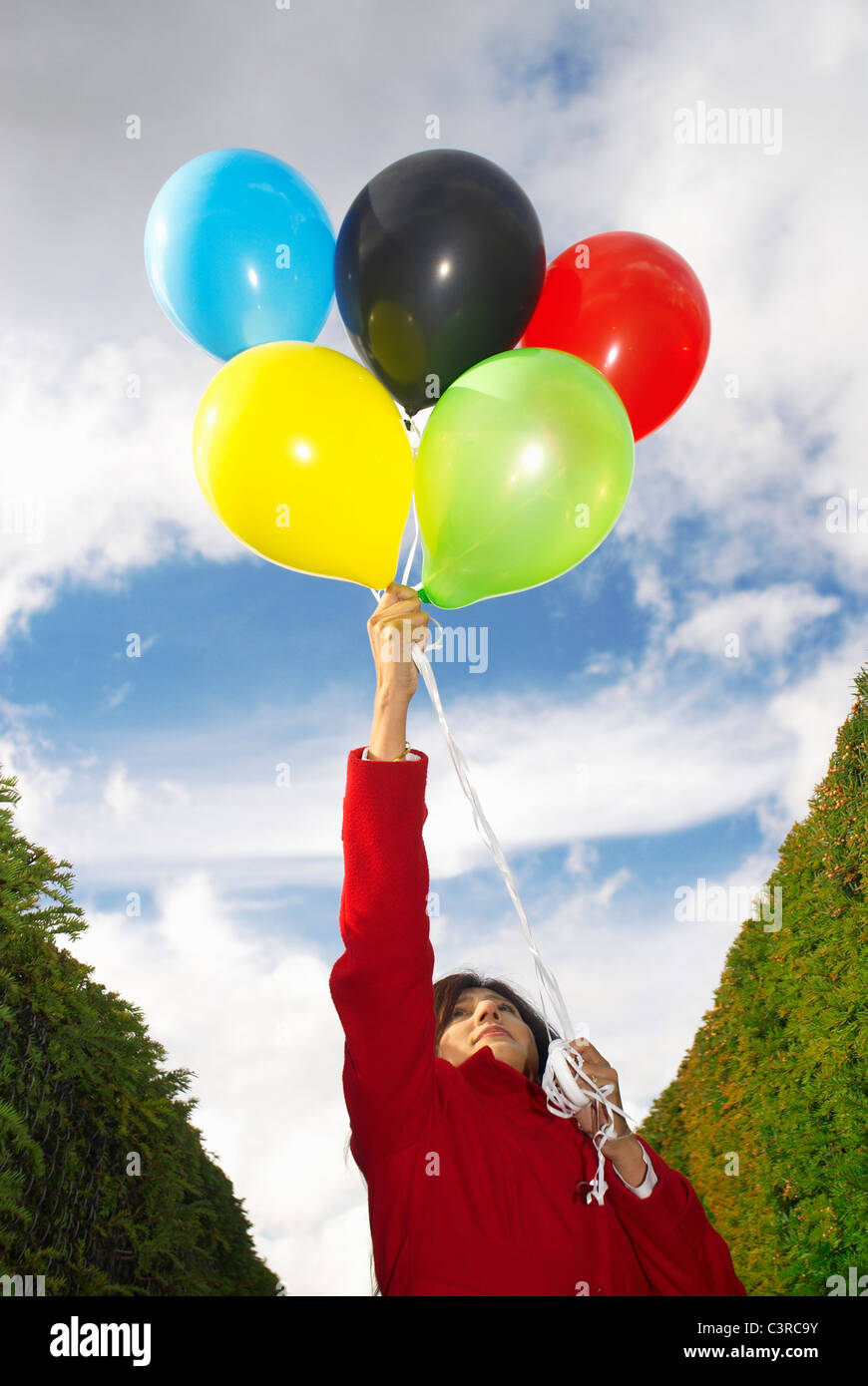 Girl holding balloons in olympic colours - Stock Image