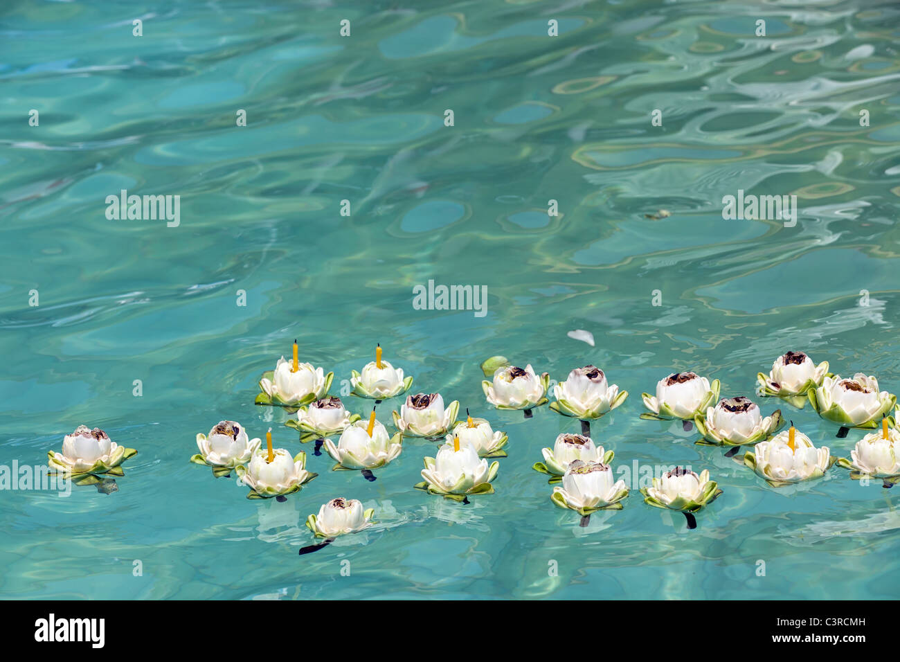 Lotus Flower With Candles Floating On Clear Blue Water Thailand