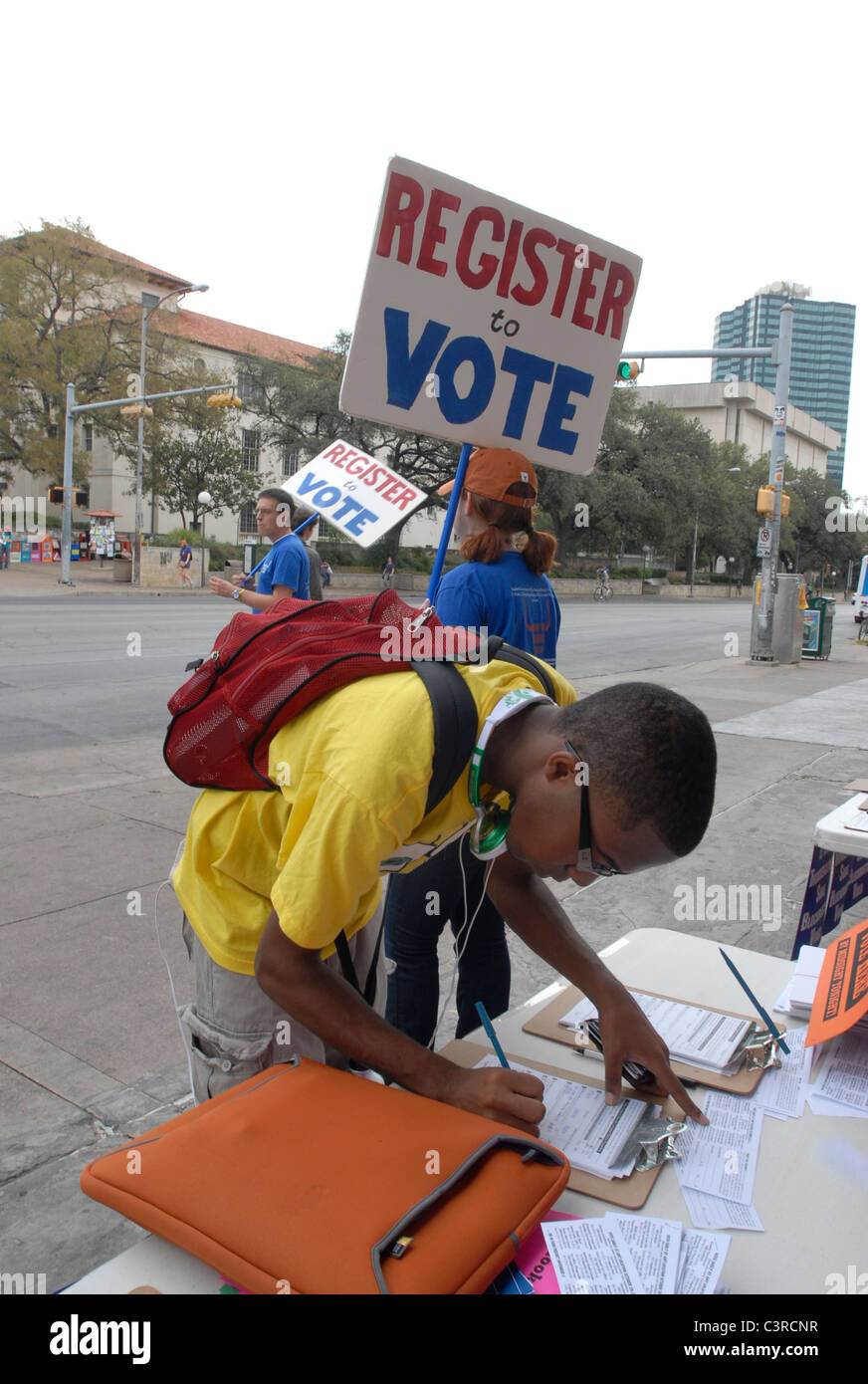 African-American college student fills fills out paperwork to register to vote as others hold up signs to encourage - Stock Image