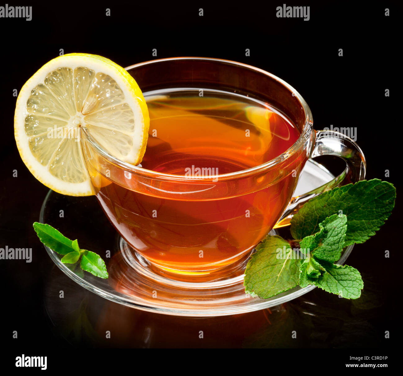 Cup tea with mint and lemon isolated on a black background. - Stock Image