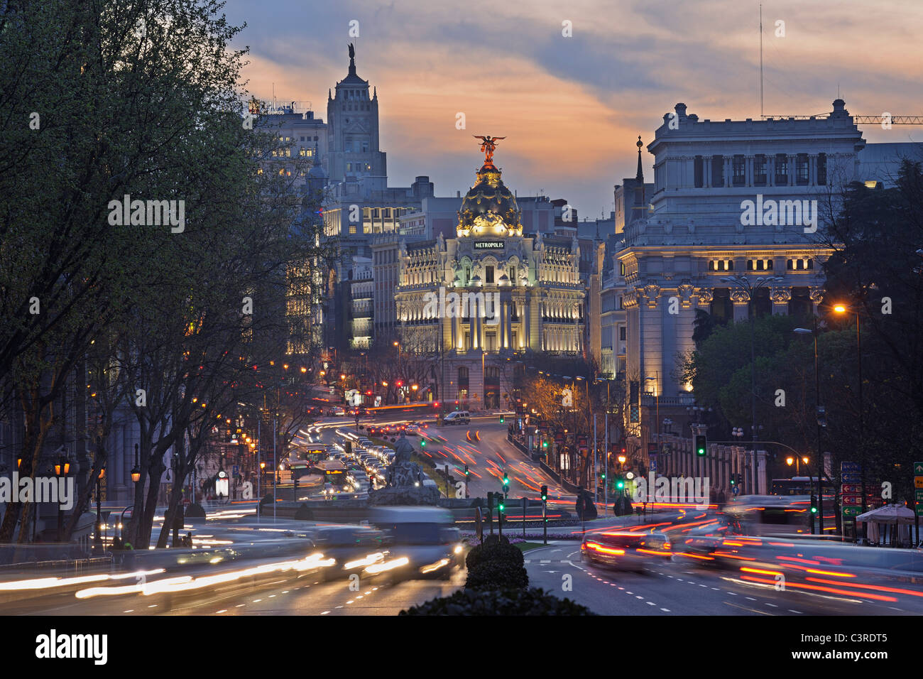 Madrid, View of Calle de Alcala and Plaza de Cibeles, Edificio Metropolis blurred traffic at dusk - Stock Image