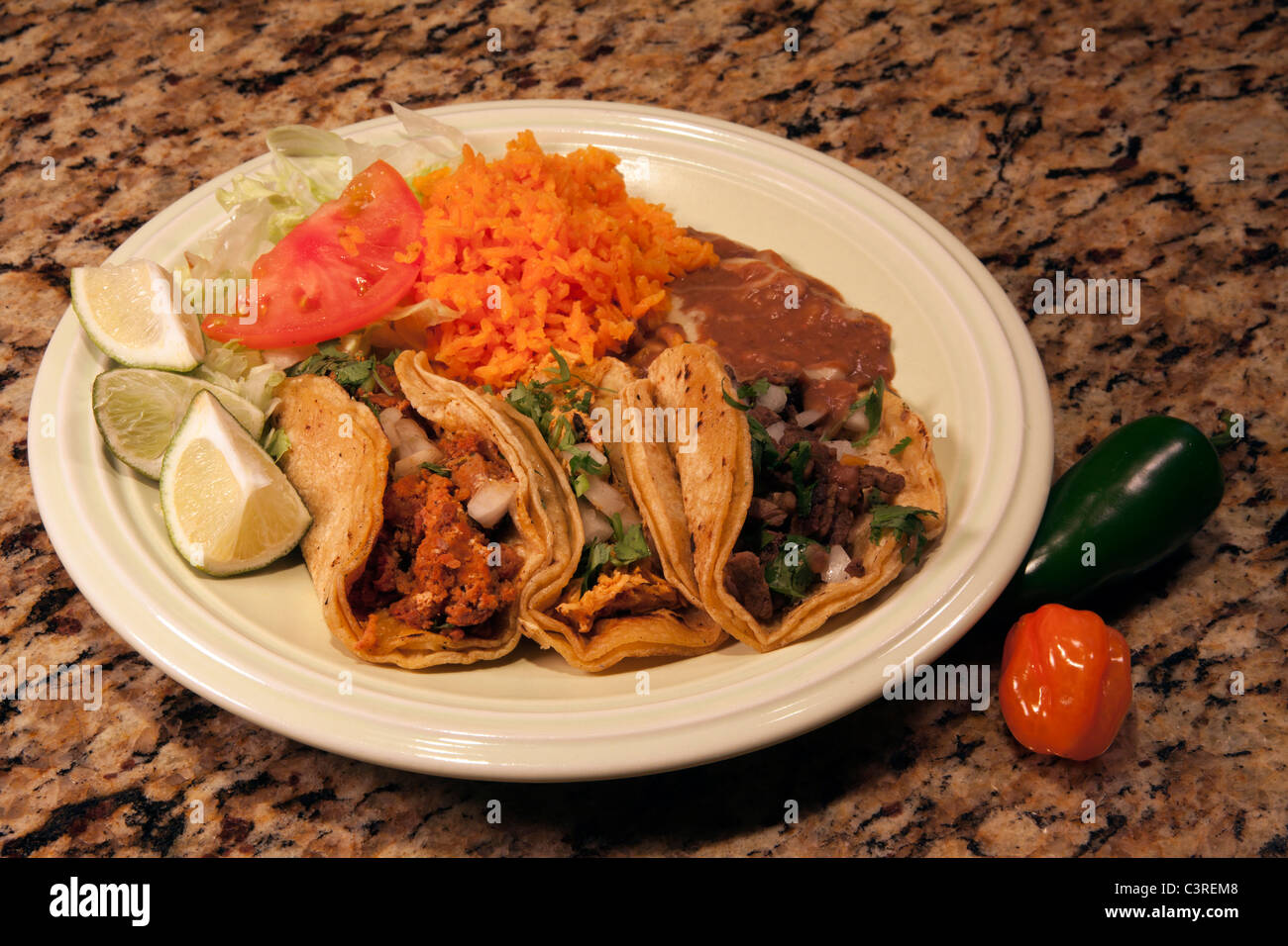 Plate of three tacos with rice and beans Stock Photo